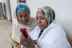 Ethiopian health care workers using red mobile phone